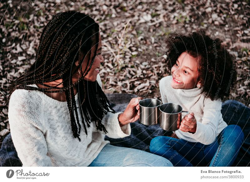 hispanic mother and afro kid girl doing picnic outdoors relaxing in nature. Autumn season. Family concept portrait daughter family mixed race motherhood