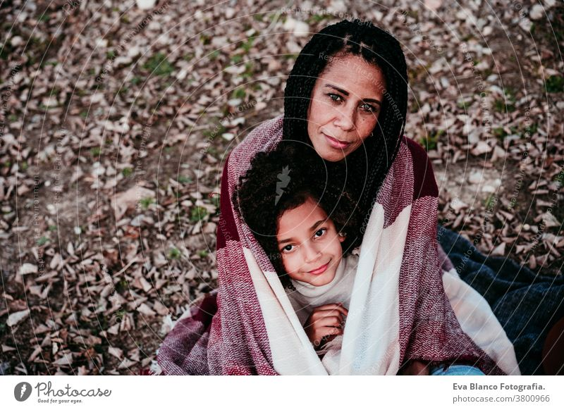 portrait of hispanic mother and afro kid girl outdoors relaxing in nature. Autumn season. Family concept daughter family mixed race motherhood childhood