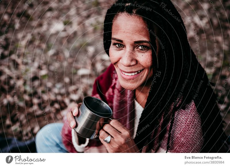hispanic mid adult woman outdoors holding a mug of water. Autumn season afro woman latin portrait sunset nature hat smile happy joy young happiness people