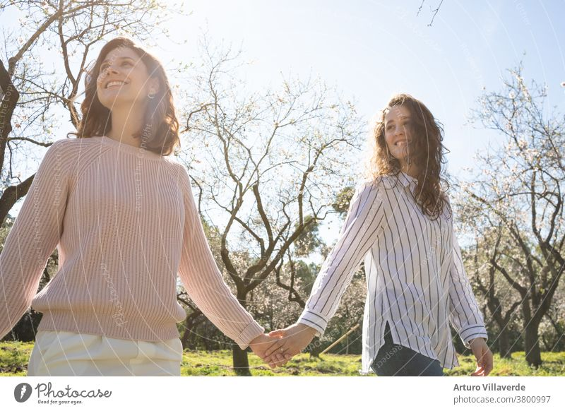 a couple of girls walking hand in hand in a park on a sunny day. They walk around smiling and happy activity background pretty Bright negligent Cheerful