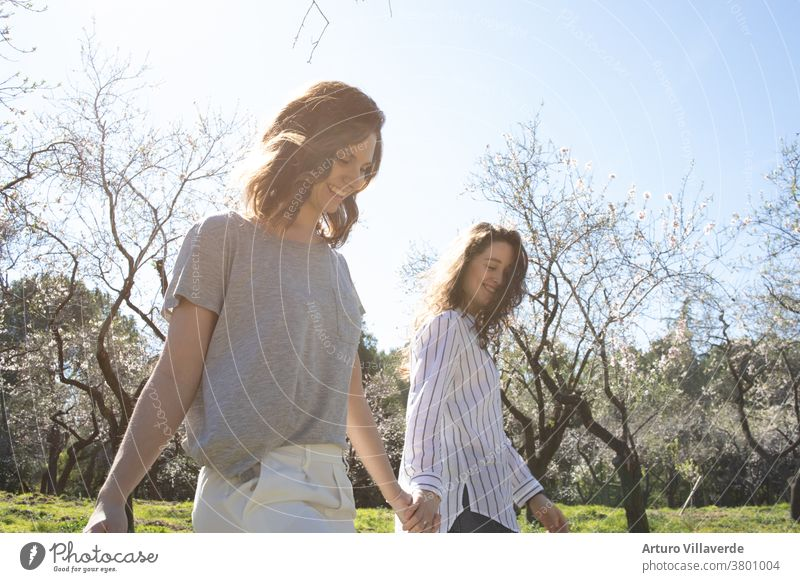 a couple of girls walk in a park hand in hand on a sunny day. They walk around smiling and happy activity background beautiful bright careless cheerful colorful