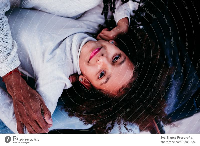 top view of afro kid girl with her mother outdoors, autumn season, family concept portrait daughter mixed race hispanic motherhood childhood parenthood