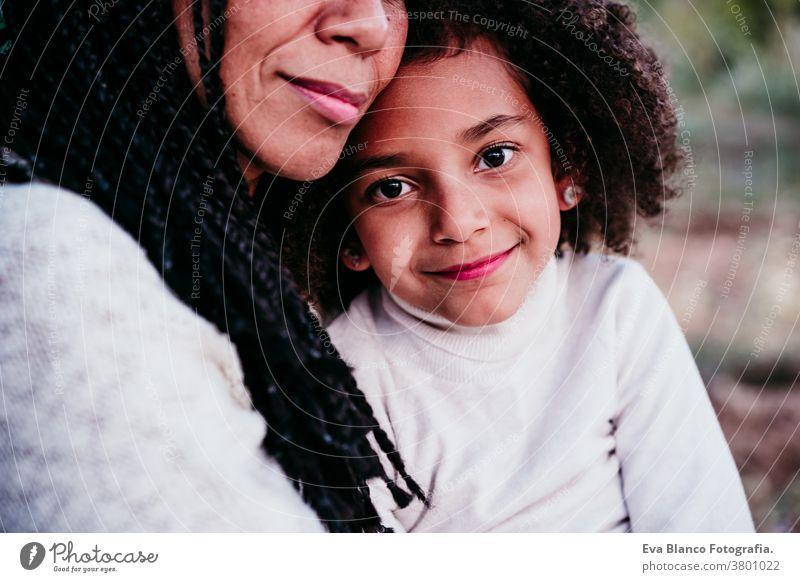 v portrait mother daughter family outdoors mixed race hispanic afro motherhood childhood parenthood single mother autumn nature park hug cheerful togetherness