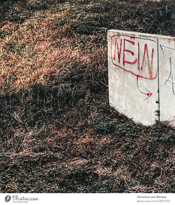 """The word """"NO"""" written with red paint is written on a low light concrete wall on a slope no Graffiti Colour Red Concrete wall Wall (building) Wall (barrier)"""