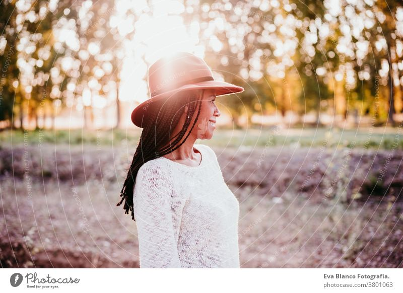 portrait of mid adult hispanic woman wearing a hat at sunset during golden hour, autumn season afro woman latin nature outdoors smile happy joy young happiness