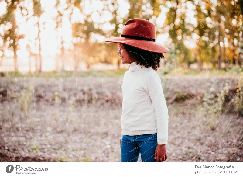 portrait of cute afro kid girl wearing a hat at sunset during golden hour, autumn season, beautiful trees background nature outdoors brown leaves