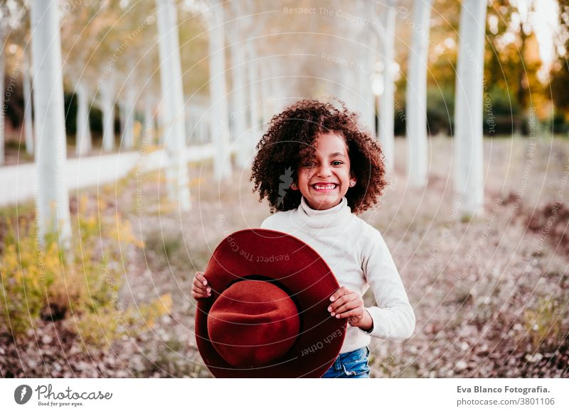 portrait of cute afro kid girl holding a hat at sunset during golden hour, autumn season, beautiful trees background nature outdoors brown leaves