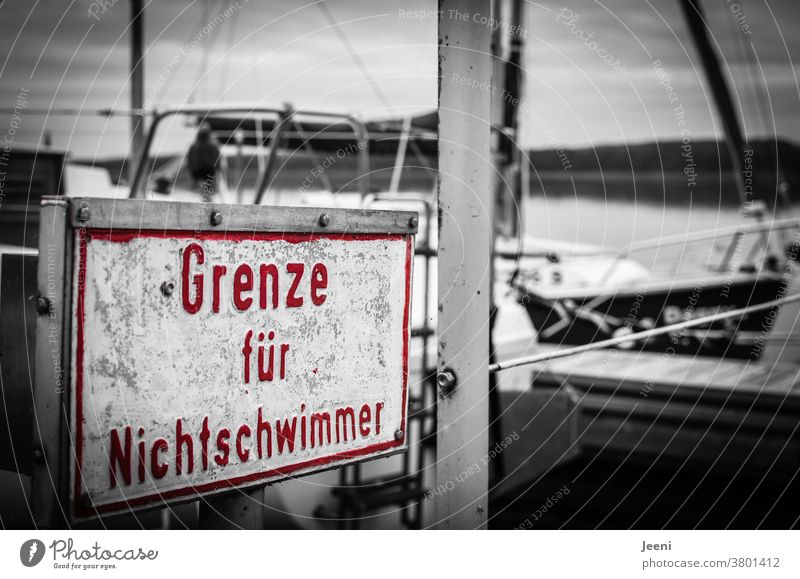 """On a jetty at the lake there is a sign in the colour red with the inscription """"Limit for non-swimmers Non-swimmer Border Water Rescue Drown First Aid Lifeguard"""