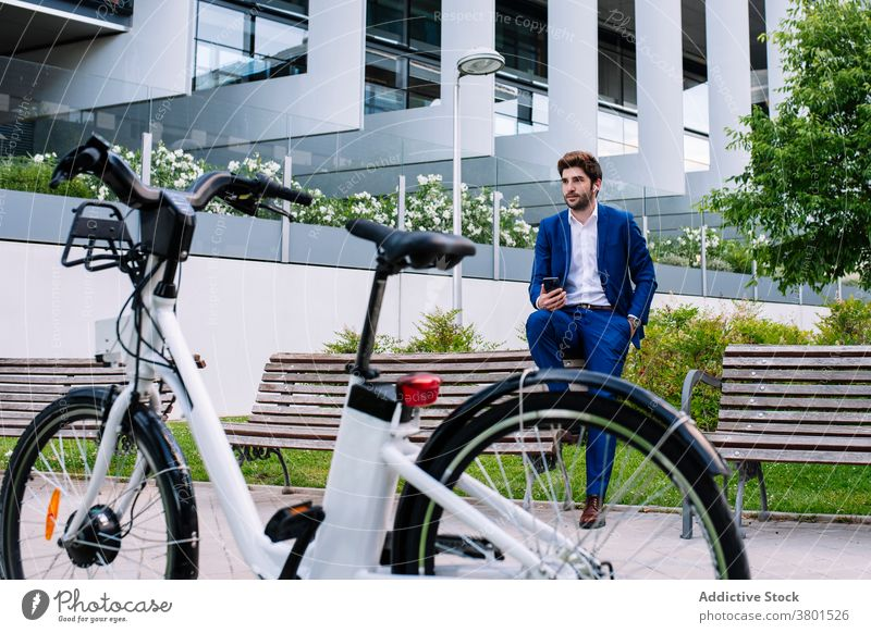 Stylish entrepreneur in formal suit looking at wristwatch on bench businessman stylish electric bike town masculine handsome device bicycle city building