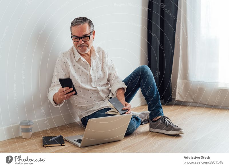 Positive mature man using smartphone and laptop on floor workspace browsing focus positive gadget device watching app concentrate casual at home busy male