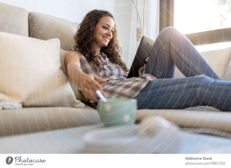 Cheerful woman browsing tablet in living room relax home entertain using message domestic weekend female internet connection social media happy device sofa