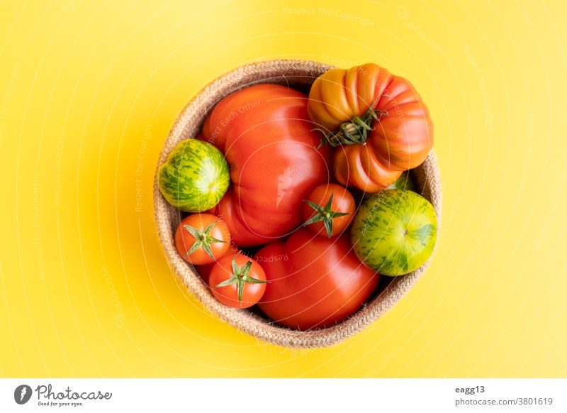 Basket with a variety of tomatoes, including: Cherry, Heirloom and Zebra on a yellow background abundance baskets cherry colourful delicious different farming