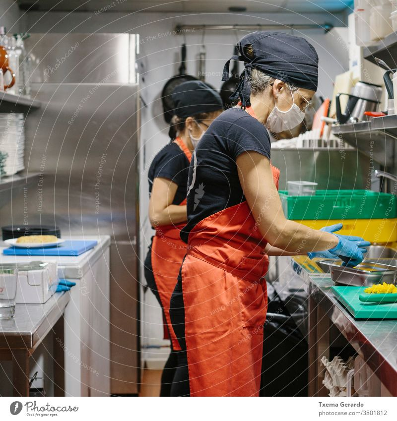 Cooks in a restaurant protected by a mask as a precaution against the coronavirus preparing takeaway food. cook kitchen salad covid-19 chef vegetarian cooking