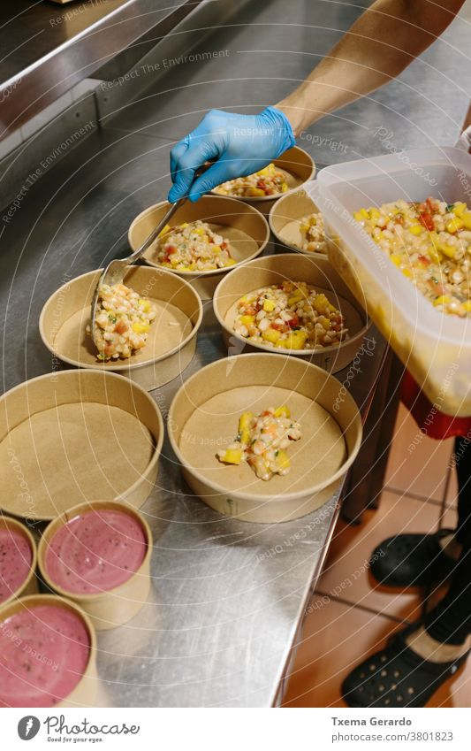 Cook preparing rice salads to take away. The containers used are compostable. takeaway food ice cream cook kitchen hand utensil glove hygienic glove restaurant