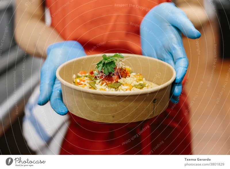 A cook presents her gourmet rice salad in a compostable take-away container takeaway food vegetarian vegan tomatoes beans apron hands gloves kitchen restaurant
