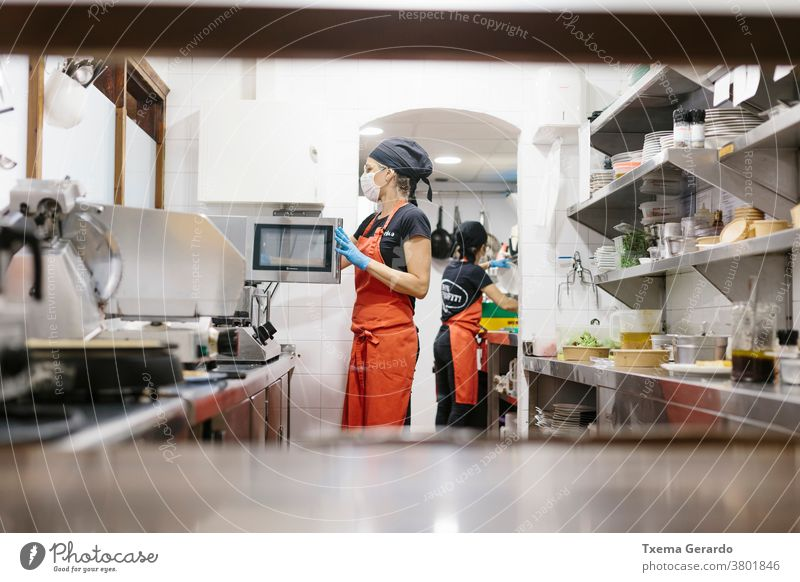 Cooks in a restaurant protected by a mask as a precaution against the coronavirus preparing takeaway food. The containers used are compostable. cook kitchen