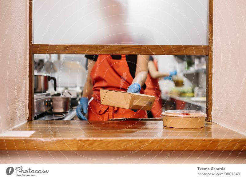 Cooks in a restaurant preparing takeaway food. The containers used are compostable. cook kitchen salad window chef vegetable cooking catering woman professional
