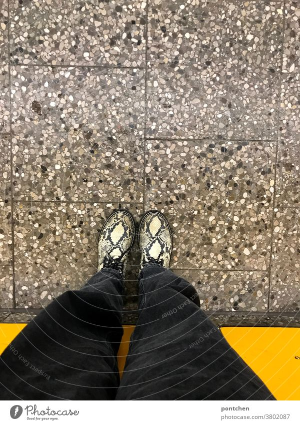 Waiting on the platform. Bird's eye view of legs and shoes in front of yellow wall Legs Footwear Fashion Platform Wall (building) Stand Human being Clothing