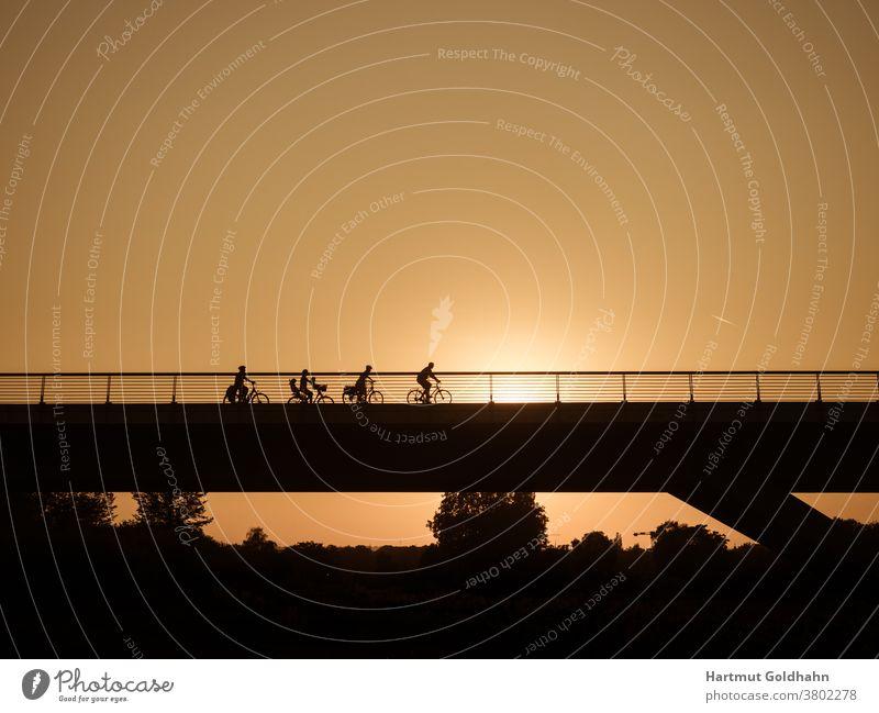 Silhouetten einer Gruppe Fahrradfahrer die kurz vor Sonnenuntergang über eine Brücke fahren. Ausflug Bauwerk Fahrad fahren Fahren Fahrräder Fahrzeug Familie