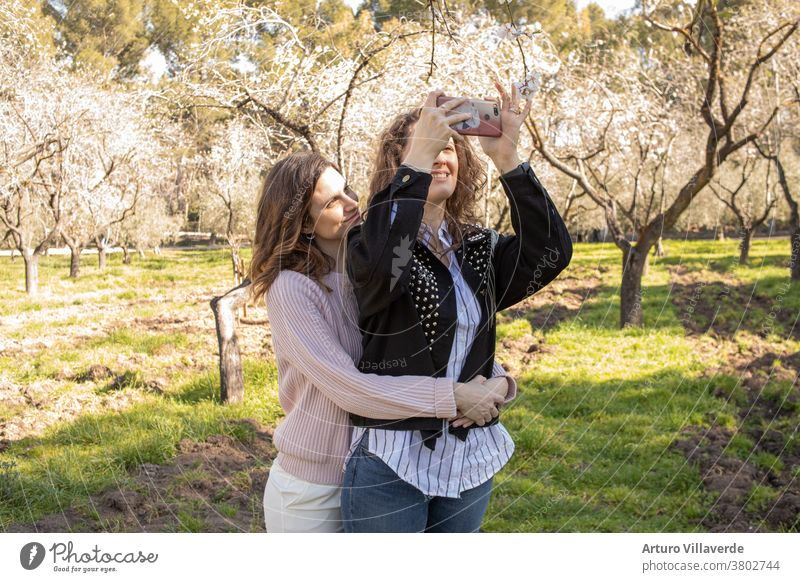 two girls in a park take cell phone selfies while hugging. They are both very pretty and smile happily. One is wearing a pink sweater and the other is wearing a studded jacket