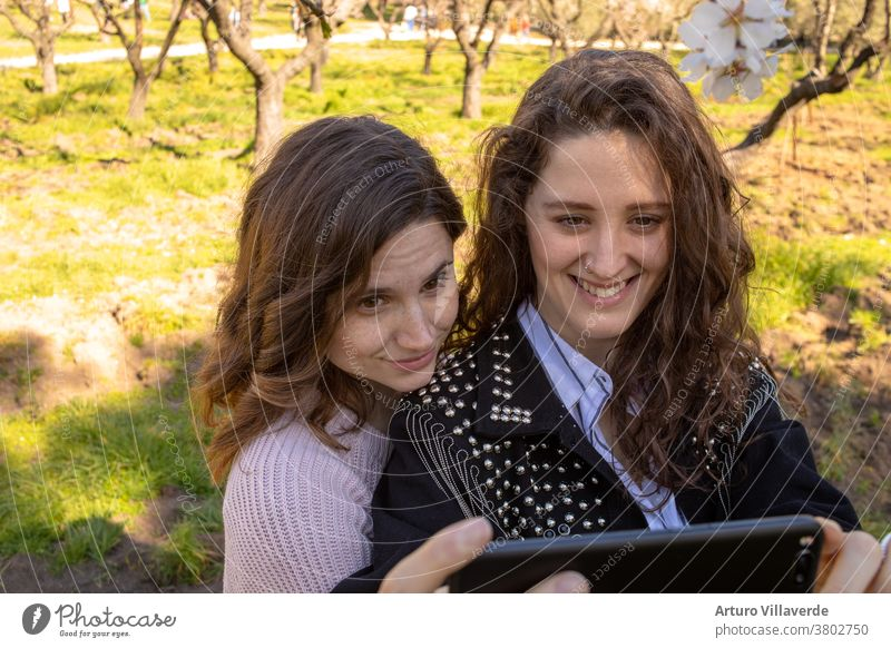 two girls in a park take mobile selfies. They are both very pretty and smile happily. One is wearing a pink sweater and the other is wearing a studded jacket