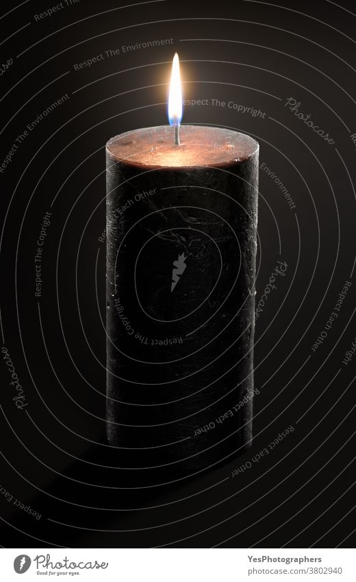 Black candle with a glowing flame isolated on a black background. Burning candle close-up advent aromatic black candle burn burning candlelight celebration