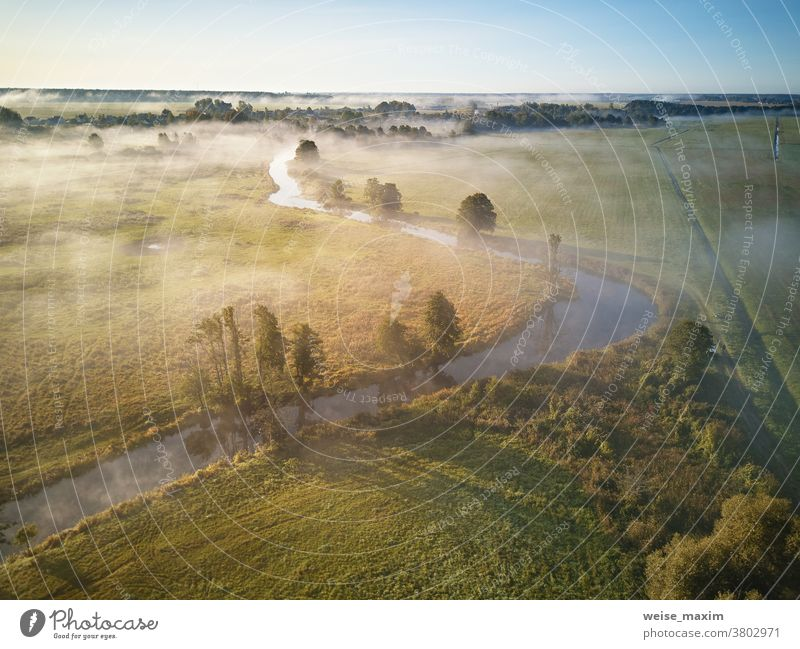 Autumn foggy sunrise aerial view. Small river with trees in meadow and field nature autumn water forest morning sunlight landscape background fall dawn mist