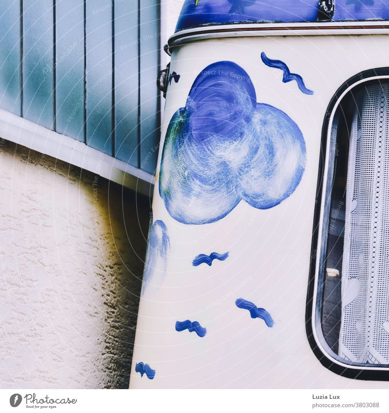 Excursion mood, blue and nostalgic: an old, beautifully painted caravan was parked close to a wall in matching colours Caravan Painted Clouds birds Drape