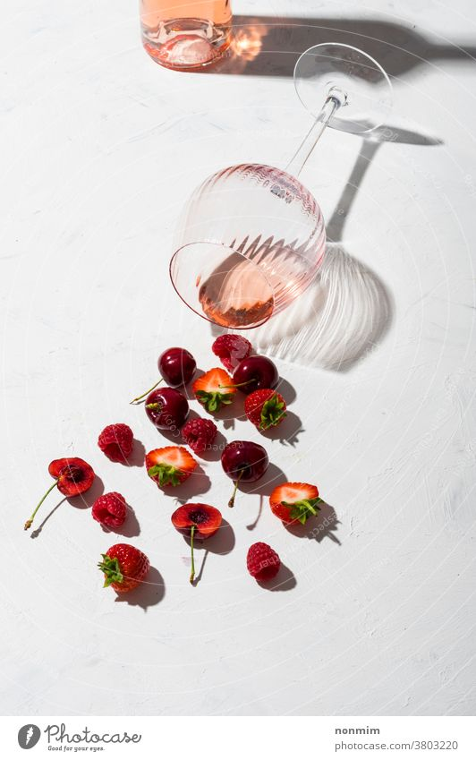 Concept composition presenting rose wine flavours of summer fruits of berries concept glass goblet flatlay berry taste shadow red alcohol bar beverage blush