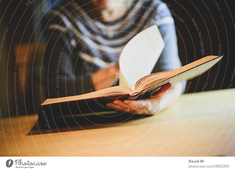 Woman browsing in a book / album Book Photo album To leaf (through a book) Hand lookup Page Reading research hands Know