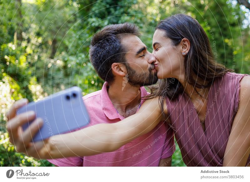 Cheerful ethnic couple taking selfie in park kiss happy smartphone cuddle date romantic love together relationship gadget mobile girlfriend boy young casual