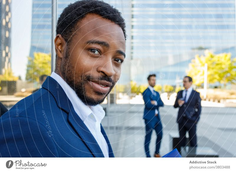 Cheerful black male employee looking at camera on street man optimist smile confident business downtown city style elegant manager businessman young