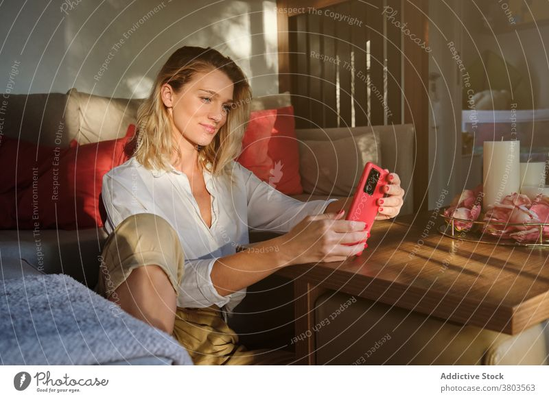 Glad woman sitting on floor and using cellphone glad browsing smartphone optimist surfing sofa gadget contemporary modern mobile smile device internet casual