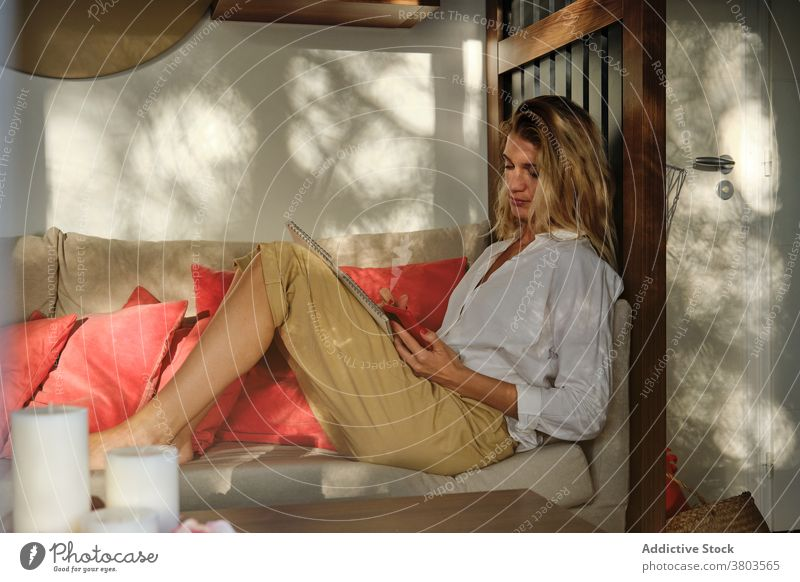 Glad woman sitting on floor and using smartphone glad browsing optimist surfing sofa gadget contemporary modern mobile smile device internet casual young