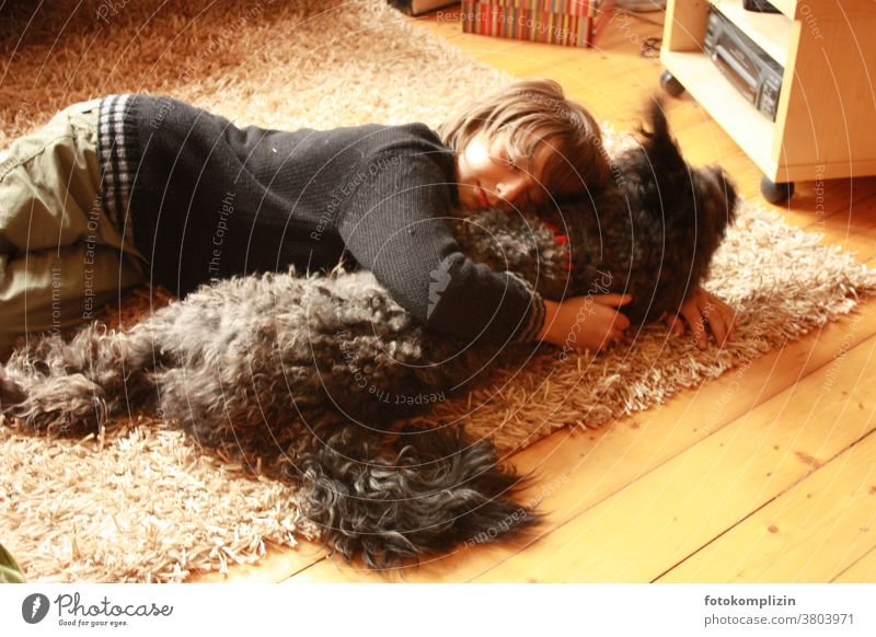 Boy lies on a carpet with a dog Pet tenderness Cuddling Infancy proximity tie Friendship dog love Humans and animals experience together in common Common ground