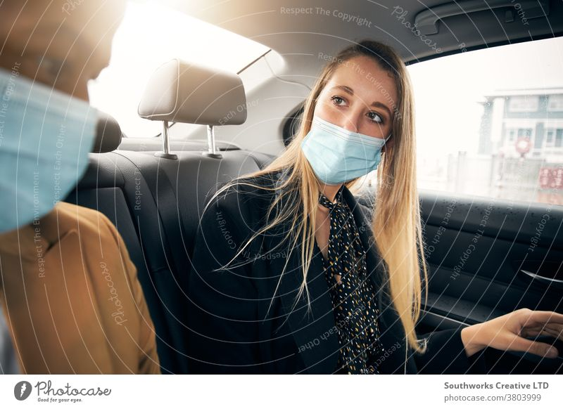 Business Couple Wearing Masks Having Conversation In Back Of Taxi During Health Pandemic business businessman businesswoman face mask face covering wearing taxi