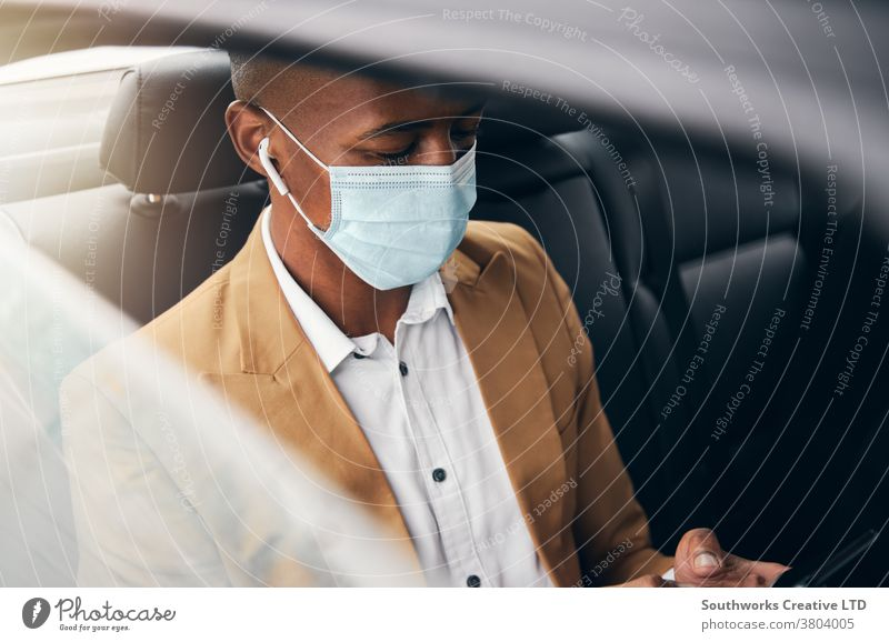 Young Businessman Wearing Mask Checking Mobile Phone In Back Of Taxi During Health Pandemic business businessman taxi face mask face covering wearing ppe cab