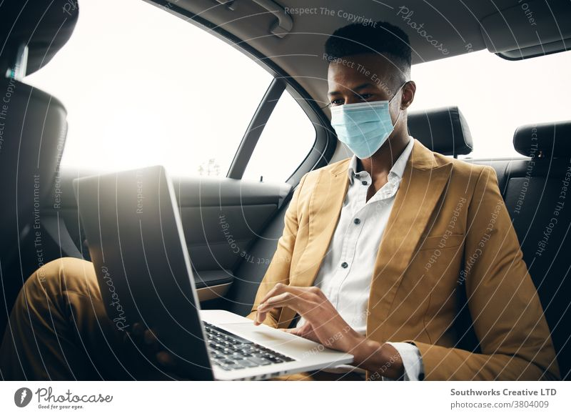 Young Businessman Wearing Mask Working On Laptop In Back Of Taxi During Health Pandemic business businessman taxi face mask face covering wearing ppe cab car