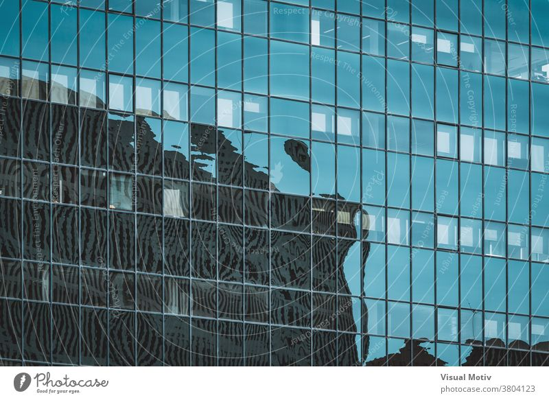 Cityscape silhouettes reflected on the glazed facade of an office building abstract reflection windows urban architecture edifice frontage structure geometric