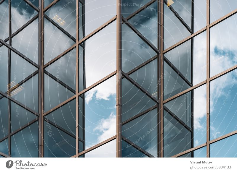 Abstract background of clouds reflected on the glazed corners of an office building facade abstract windows urban architecture edifice frontage structure