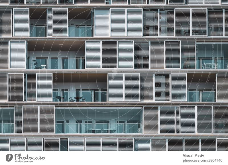 Frontal geometrical view of the shutters and balconies of an urban building arranged in continuous rows facade architecture metropolitan edifice structure