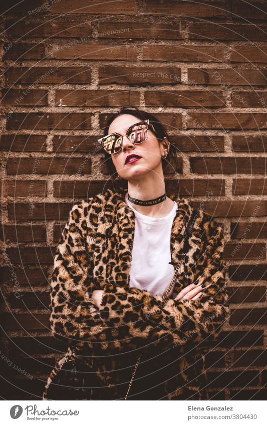 Stylish portrait of young serious model with crossed arms wearing trendy leopartd print faux fur coat, fashion sunglasses, posing on red brick wall texture grunge background