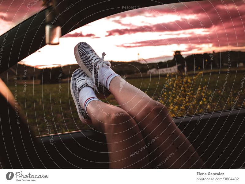 young woman with sneakers with feet propped on the car window at sunset legs journey people lifestyle sunlight road trip footwear travel fun girl tourist child