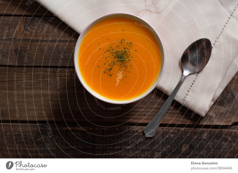 pumpkin cream with chives and parsley on wooden table puree dinner plate dish restaurant delicious ingredient thanksgiving napkin thyme festive vegan