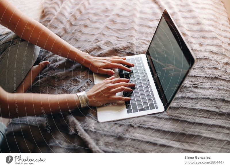 Woman's hands typing on laptop keyboard in the cozy bedroom woman working sitting macbook businesswoman using computer home female person technology lifestyle