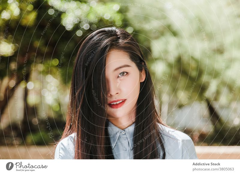 Dreamy young ethnic female in summer park woman gorgeous relax portrait cover eye style feminine appearance personality model fashion asian dark hair long hair