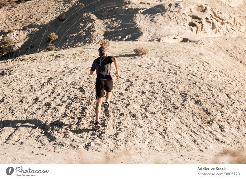 Anonymous sportsman jogging on sandy terrain in mountainous terrain run semi desert hill training active jogger healthy nature wellbeing exercise workout male