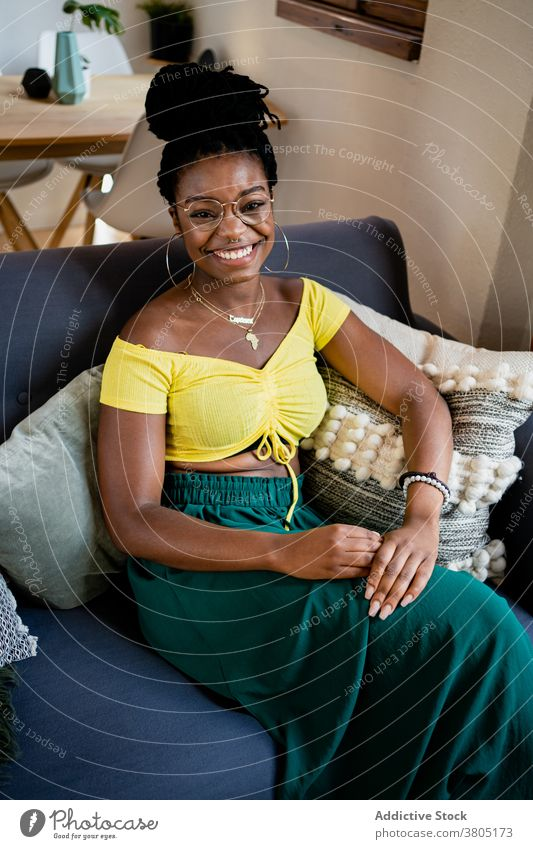 Cheerful black woman resting in living room toothy smile happy at home style fashion weekend free time sofa female african american eyeglasses apartment flat