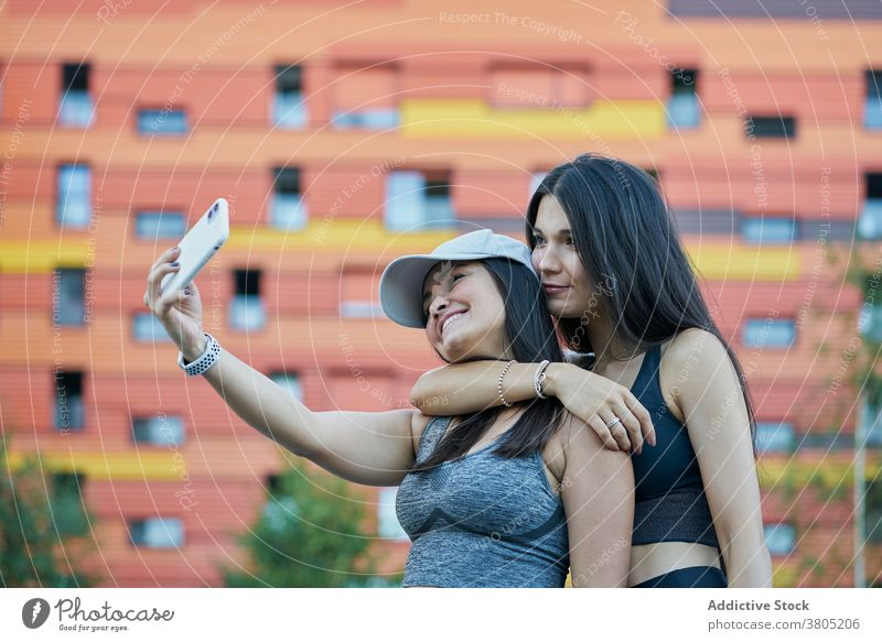 Positive young ethnic women taking selfie on street smartphone together smile cuddle friendship positive social media using mobile brunette long hair cheerful