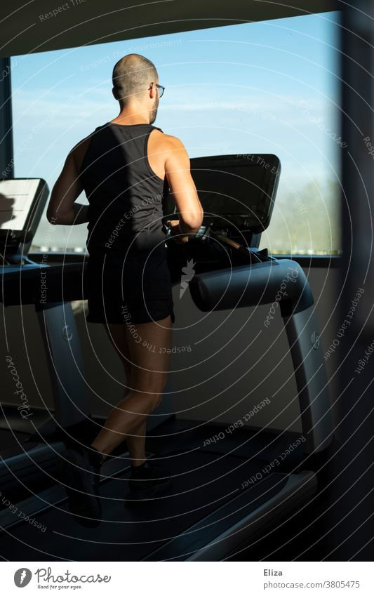 Man exercising on a treadmill with window view in the gym Moving pavement Walking Fitness centre Window sunshine Sports workout Movement Jogging inside